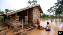 Kongvilay Inthavong and his wife Thongla clean up their house as the floodwaters start to recede in Sanamxay district, Attapeu province, Laos on Thursday, July 26, 2018. Authorities and the builder are investigating why a dam in southeastern Laos collapsed earlier this week, killing at least two dozen people and leaving over a hundred missing. (AP Photo/Hau Dinh)