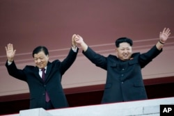 10일 북한 노동당 창건 70주년 열병식에 참석한 김정일 북한 국방위원회 제1위원장이(오른쪽) 중국 대표단을 이끌고 방북한 류윈산 공산당 중앙정치국 상무위원과 손을 들어보이고 있다.