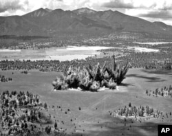 This 1968 photo provided by the U.S. Geological Survey Astrogeology Science Center shows craters being created in a volcanic cinder field east of Flagstaff, Ariz.