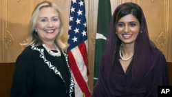 U.S. Secretary of State Hillary Rodham Clinton, left, shakes hand with Pakistani Foreign Minister Hina Rabbani Khar following their joint news conference in Islamabad, Pakistan, Friday, Oct. 21, 2011. Clinton said Friday that extremists have been able to