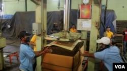 Pekerja mengepak tembakau yang akan dikirim ke beberapa industri besar rokok di Indonesia. (Foto: VOA/Petrus Riski).