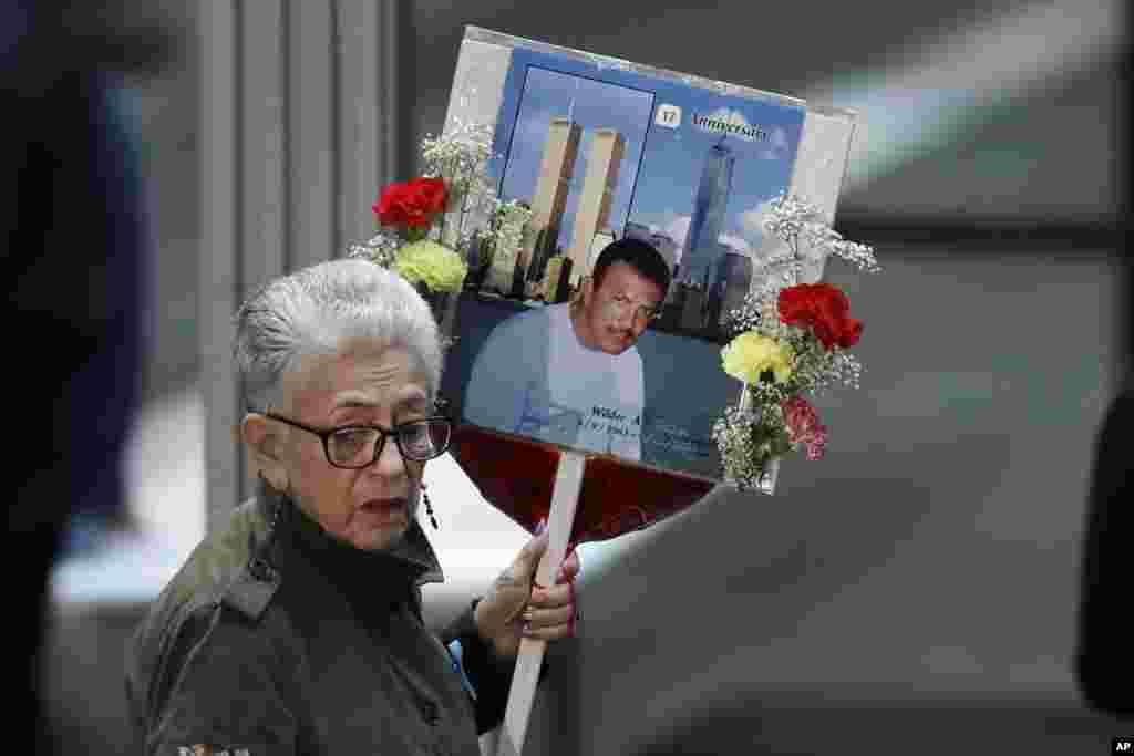 Seorang perempuan membawa foto Wilder Gomez, seorang bartender di restoran Windows on the World di lantai 103 di World Trade Center, dalam upacara peringatan 17 tahun serangan teror terhadap Amerika Serikat, 11 September 2018 di New York.