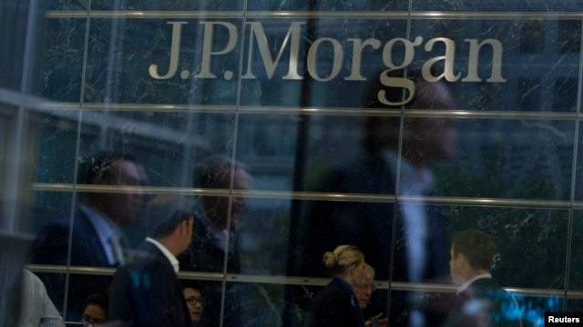 FILE - Workers are reflected in the windows of JP Morgan Chase offices.