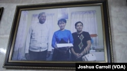 A picture hanging in Ko Ni's family home shows him and his wife (right) posing with Aung San Suu Kyi.