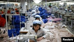 FILE - North Korean employees sew in a South Korean-owned company at the Kaesong industrial park just north of the demilitarized zone, December 2013.