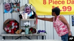 A woman touches a makeshift memorial for Alton Sterling, outside a convenience store in Baton Rouge, Louisiana, July 6, 2016. Sterling was shot and killed by police outside the store.