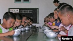 FILE - North Korean children eat lunch at a government-run kindergarten in Taedong county in south Pyongan province, July 18, 2005.