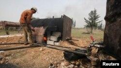 Hemwelatîyekî Sûrî nefta xav pak dike.
