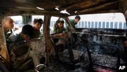 FILE - Yemeni boys look at a vehicle destroyed during a police raid on an al-Qaida militant hideout in the Arhab region, north of Sanaa, Yemen, May 27, 2014.