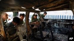 Các bé trai Yemen nhìn vào một chiếc xe bị phá hủy trong một cuộc đột kích của cảnh sát vào nơi ẩn náu của các chiến binh al-Qaida ở vùng Arhab hôm 27/4/2014.