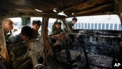 FILE - Yemeni boys look at a vehicle destroyed during a police raid on an al-Qaida militant hideout in the Arhab region, north of Sana'a, Yemen, May 27, 2014.