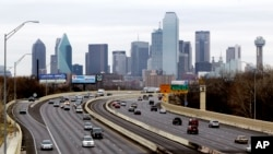 This Friday, Jan. 14, 2011, file photo shows highway traffic with the Dallas skyline in the background. (AP Photo/Tony Gutierrez, File)