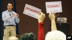 "Audience members hold signs reading ""DISAGREE"" as U.S. Rep. Scott Perry, R-Pa., speaks during a town hall meeting, March 18, 2017, in Red Lion, Pa. Perry's event turned contentious in his conservative south-central Pennsylvania district over questions about his support for President Donald Trump's budget proposal and immigration plans and for undoing former President Barack Obama's signature health care law."