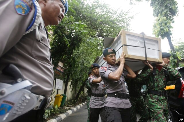 FILE - Indonesian police officers and soldiers carry one of the coffins prepared for the victims of a military helicopter which crashed in Poso, Central Sulawesi, at hospital in Jakarta, Indonesia, March 21, 2016.