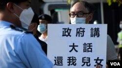 懷疑被送中港人鄭子豪父親在警員包圍下手持標語,質疑港府說謊要求中國當局釋放12港人。(美國之音湯惠芸拍攝)