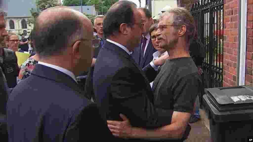 François Hollande, qui s'est rendu sur les lieux, s'entretient avec le maire de la commune normande, Hubert Wulfranc, peu après le drame, le 26 juillet 2016.