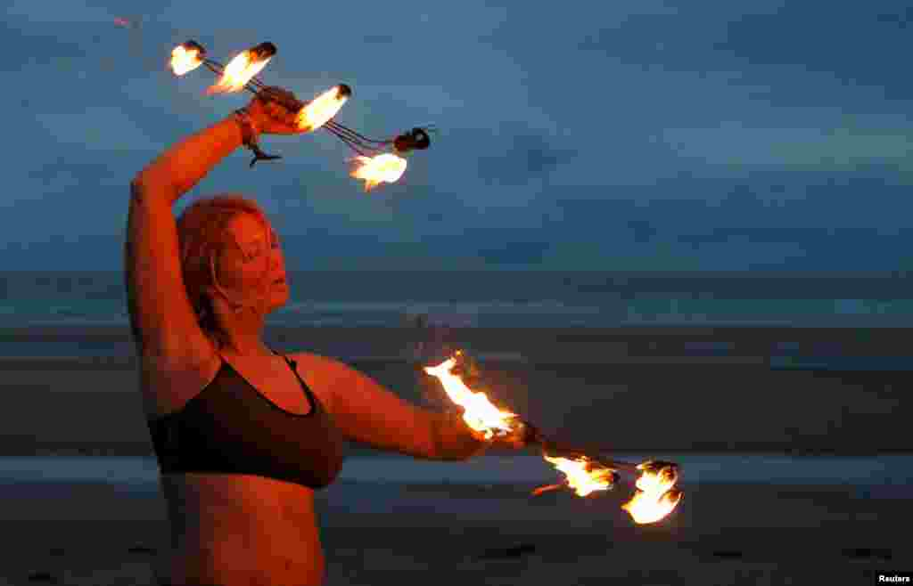 A participant in the annual North East Skinny Dip performs a fire display at Druridge Bay, Britain.