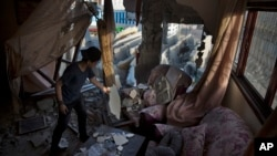 Seorang anak Palestina memeriksa puing-puing rumahnya pasca serangan udara Israel atas kota Gaza, Jalur Gaza bulan lalu (foto: dok).