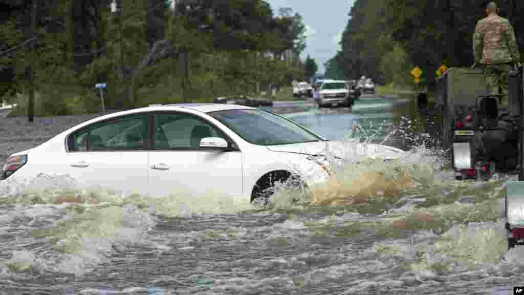 Un véhicule abandonné dans l'eau sur la route 190, après de fortes pluies qui ont inondé la région, le 14 août 2016.