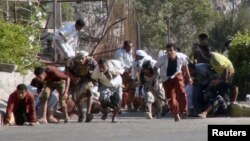 FILE – People run for cover amid gunfire at an army base in Aden, Yemen, March 25, 2015. The U.N. Security Council is meeting to discuss a humanitarian pause in fighting against Houthi rebels.