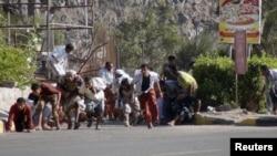 Yemenitas buscan refugio durante un tiroteo en una base militar en el puerto de Adén, en Yemen.