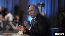 Russian President Vladimir Putin takes part in a televised news conference in Moscow, Dec. 19, 2013.