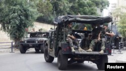 Lebanese Army soldiers sit in their military vehicles as they are deployed to secure the area near the French embassy in Beirut, September 21, 2012.