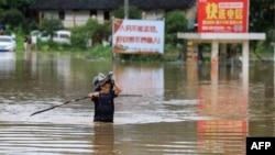 Seorang pria berjuang mengarungi banjir yang menggenangi jalan di Rongan, Wilayah Guangxi di selatan China setelah hujan lebat melanda wilayah itu, 9 Juni 2019. (Foto: AFP)
