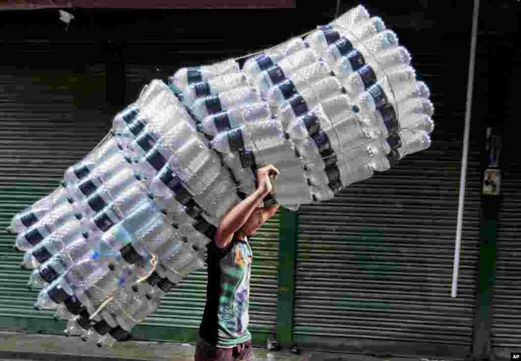 پسرک کارگر هندی بطری های خالی آب را حمل می کند.