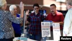 Workers take an oath prior to opening a polling station during voting in the 2016 presidential election in Las Vegas, Nevada, Nov. 8, 2016.