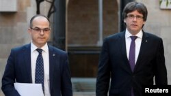 FILE - Catalan President Carles Puigdemont, right, walks with Catalan Government Presidency Councillor Jordi Turull in Barcelona, Spain, Oct. 17, 2017. Catalonia's Parliament votes Thursday for a regional president, and Turell is the third candidate for that post.