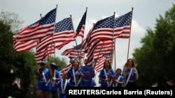 Des gens portent des drapeaux américains pendant qu'ils participent à un défilé lors des célébrations de la fête de l'indépendance du 4 juillet à Washington, D.C., États-Unis, le 4 juillet 2019. REUTERS / Carlos Barria