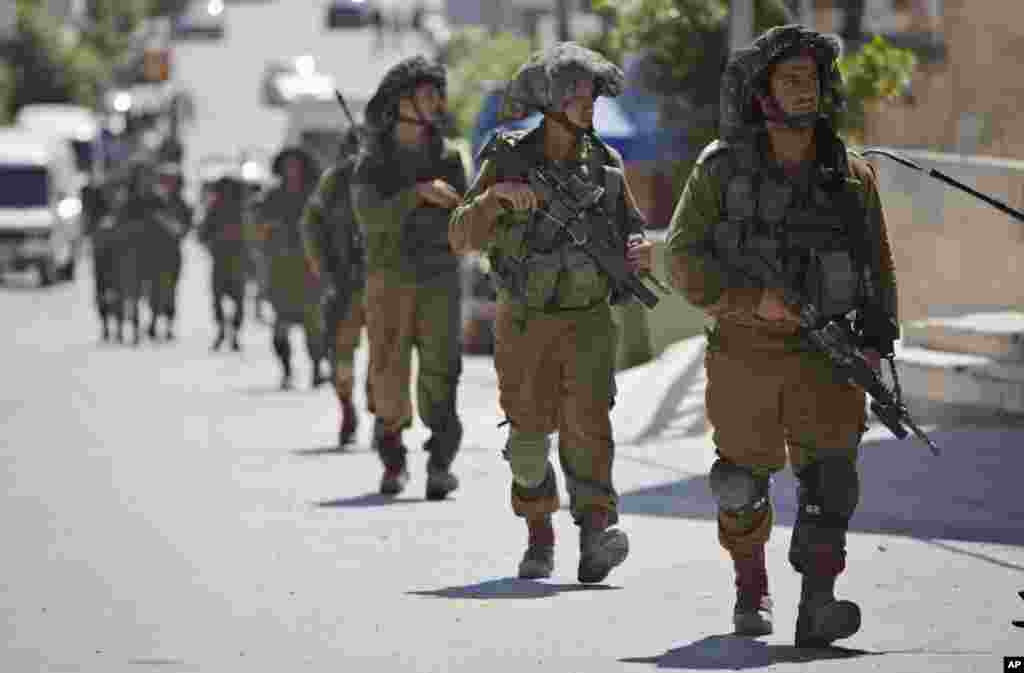 Israeli soldiers patrol during a search for three missing Israeli teenagers in the village of Taffouh near the West Bank city of Hebron, June 18, 2014.