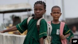 Young Nigerian school girls walk near a bus park. Often girls are forced to give up their educational aspirations (File Photo).