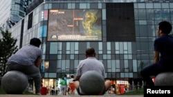 北京居民坐在一家商场外观看电视新闻节目。(2016年7月16日)