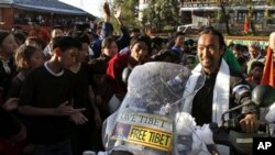 Lhakpa Tsering, on the motorbike, is greeted by school children as he arrives at the Tibetan Children's Village School in Dharmsala, India, Thursday, Oct. 28, 2010. Tsering, a Tibetan refugee living in New York, arrived here after traveling on his motorbi