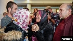 Reaksi pengungsi Suriah, Baraa Haj Khalaf (kiri), saat bertemu ibunya, Fattoum (tengah), dan ayahnya Khaled, setelah tiba di Bandara Internasional O'Hare di Chicago, 7 Februari 2017.
