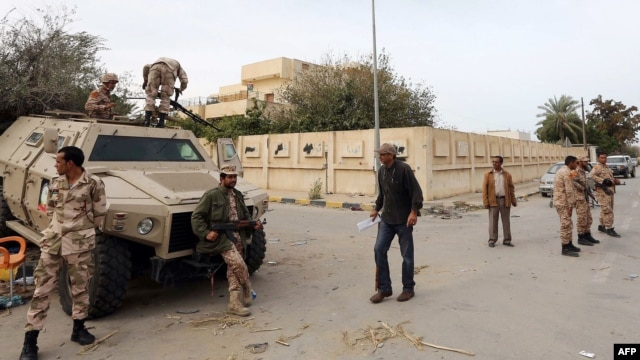 Libyan soldiers, some on an armored personnel carrier (APC), deploy in a Tripoli's neighborhood after militias were ordered to leave the capital following deadly weekend clashes, Nov. 18, 2013.