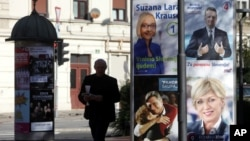A man walks past presidential election campaign posters in Ljubljana, Slovenia, Oct. 19, 2017.