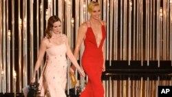 """Emily Blunt (kiri) dan Charlize Theron saat membacakan pemenang Oscars 2016 di Los Angeles, 28 Februari lalu. Kedua aktris ini tampil sebagai pemeran utama dalam """"The Huntsman: Winter's War."""""""