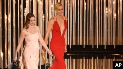 "FILE - Emily Blunt, left, and Charlize Theron present an award at the Oscars in Los Angeles, Feb. 28, 2016. The actresses appear in ""The Huntsman: Winter's War."""