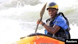David Egesa, 40, a member of Uganda's kayaking team, paddles against waves during a team practice session in the River Nile in Jinja, east of Uganda's capital, Kampala, Aug. 19, 2015.