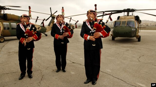 A Jordanian military band plays bagpipes and drums in front of UH-60A helicopters, better known as Black Hawks, delivered from the United States to Jordan's Marka Airport, in Amman, March 3, 2016.