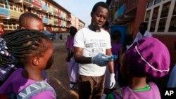 Wani Malami yana amfani da na'urar auna zafin jiki domin neman alamun cutar Ebola.