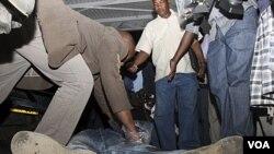Seorang polisi Kenya memeriksa kantung celana seorang pria yang tewas akibat ledakan granat di Nairobi (10/3).