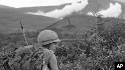 A U.S. Marine pinned down by sniper fire, looks back to check on his buddies as white phosphorous artillery rounds mark major Viet Cong position, action took place 15 miles south, southwest of Da Nang, Jan. 29, 1967.