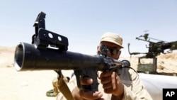 一名叛軍戰鬥人員正在檢查一批火箭發射器。這批武器是2011年6月30日從約黎波里以南大約100公里處忠於卡扎菲近的軍隊手中繳獲的