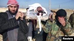 Para pejuang lasykar pembebasan Suriah mengangkut komandan mereka yang tewas di kota Qusair, provinsi Homs (25/3). Pertempuran meningkat selama dua pekan terakhir di kota ini.
