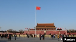 FILE - A Chinese flag flutters against the blue sky in Tiananmen Square in Beijing, China, Dec. 24, 2017.