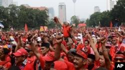 穿红衣的示威者在吉隆坡举行大游行,声援被侵吞公款丑闻困扰的总理纳吉布。